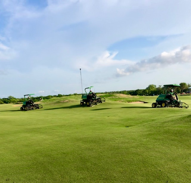 The John Deere fleet takes to the course to mow in between downpours.